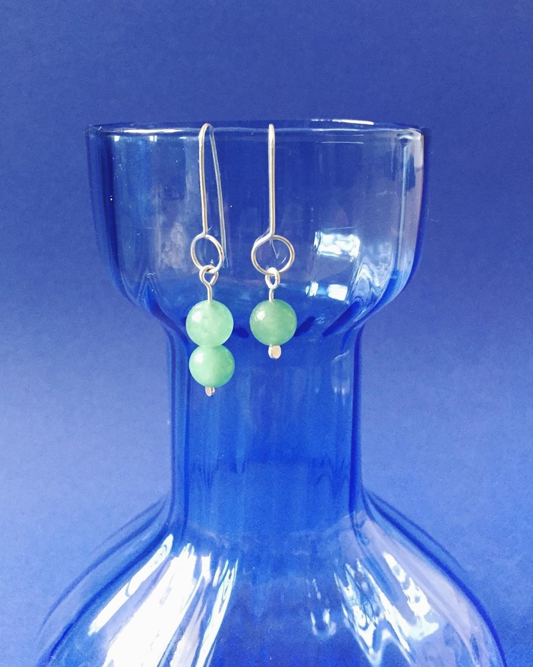 close up of jade earrings, …